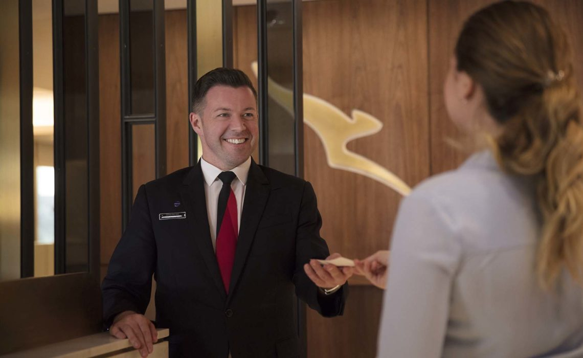 Passenger handing over boarding pass to a Qantas staff member at the reception of the Qantas business lounge in London