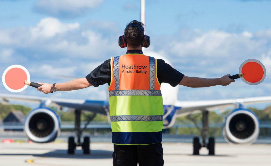 Heathrow, airfield, airfield ops marshaller guiding aircraft on apron, Sep 2018.