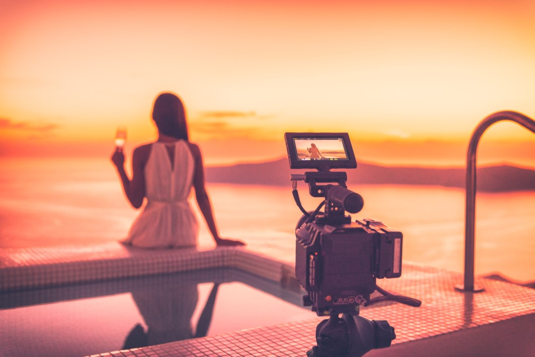 Videography behind the scene video camera shooting movie at sunset beach resort hotel filming actress woman acting, luxury travel. Professional videography equipment shooting outdoor at sunset.